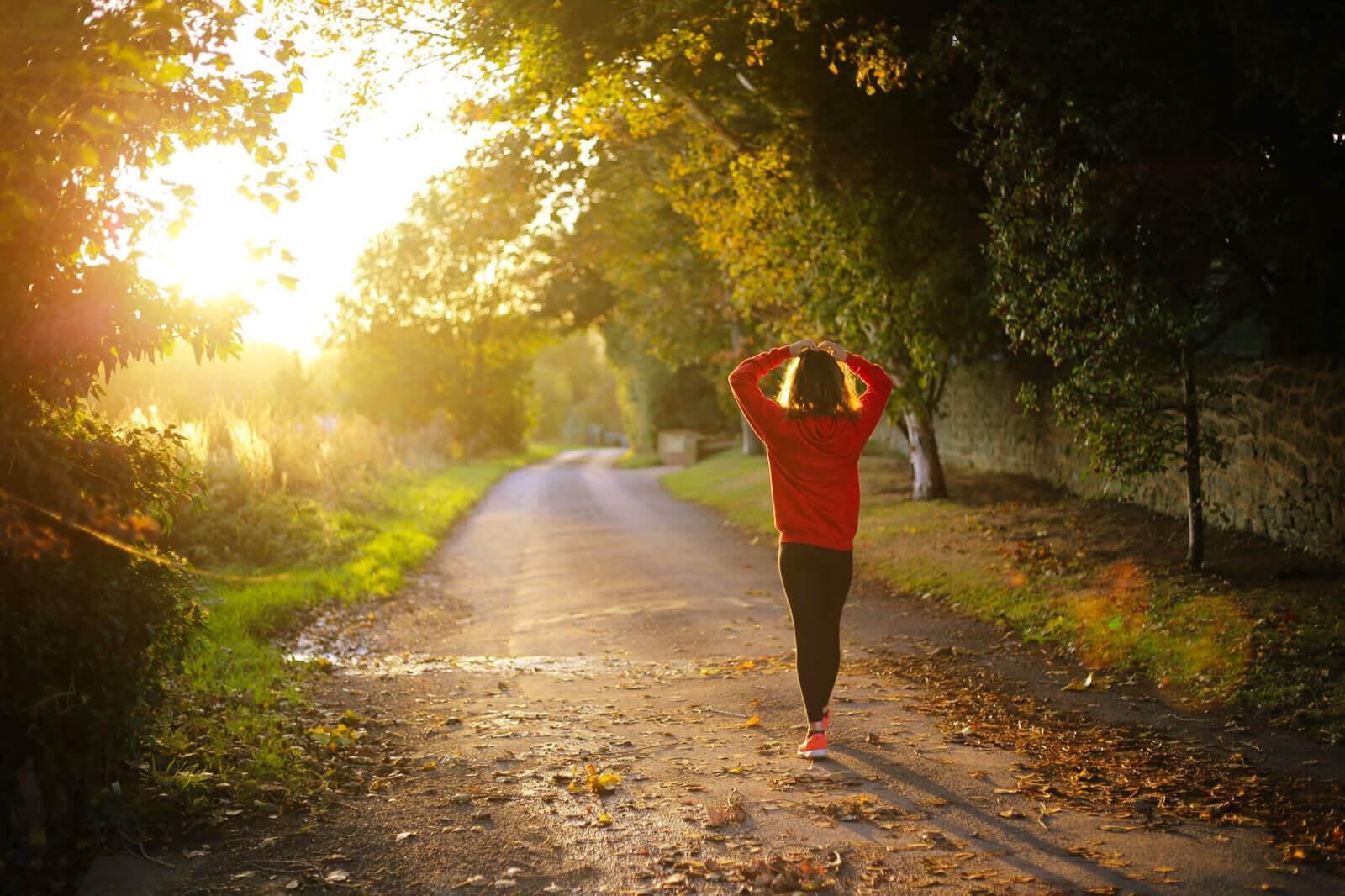 Lady walking along country road at sunrise
